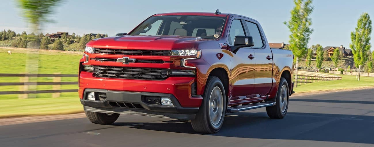 A red 2020 Chevy Silverado 1500 is driving past a grassy field that's fenced in near Bethlehem, PA.