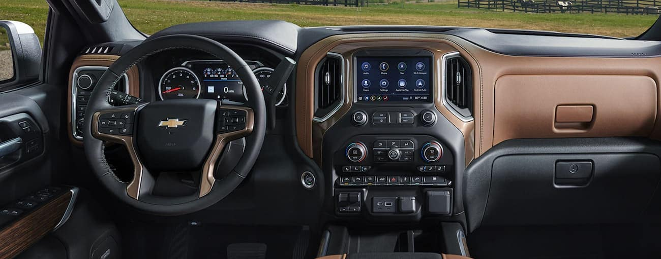 The front black and brown leather interior of the 2020 Chevy Silverado 1500 is shown with an infotainment system and drivers display.