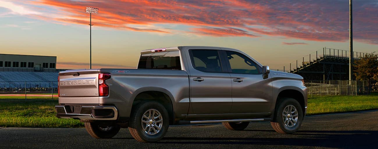 A silver 2020 Chevy Silverado 1500, which wins when comparing the 2020 Chevy Silverado vs 2020 Ford F-150, is parked in front of a football field at sunset near Bethlehem, PA