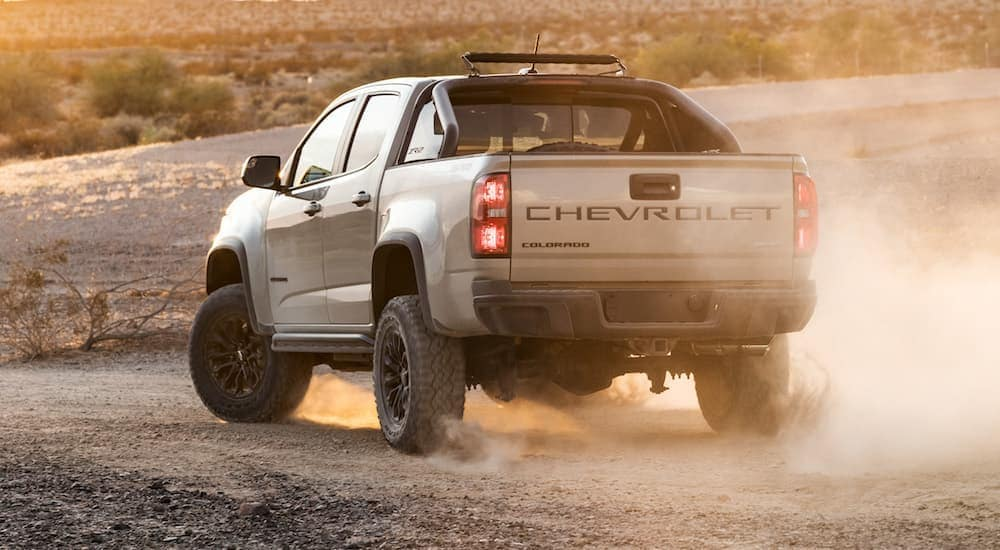 A tan 2021 Chevy Colorado ZR2, which has a factory suspension lift kit installed, is driving on a dirt road with a dust cloud rising behind it.