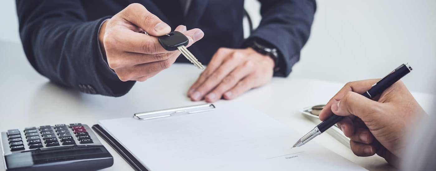 A closeup is shown of a salesman's hands giving keys to a buyer signing paperwork at our Bethlehem, PA dealership.