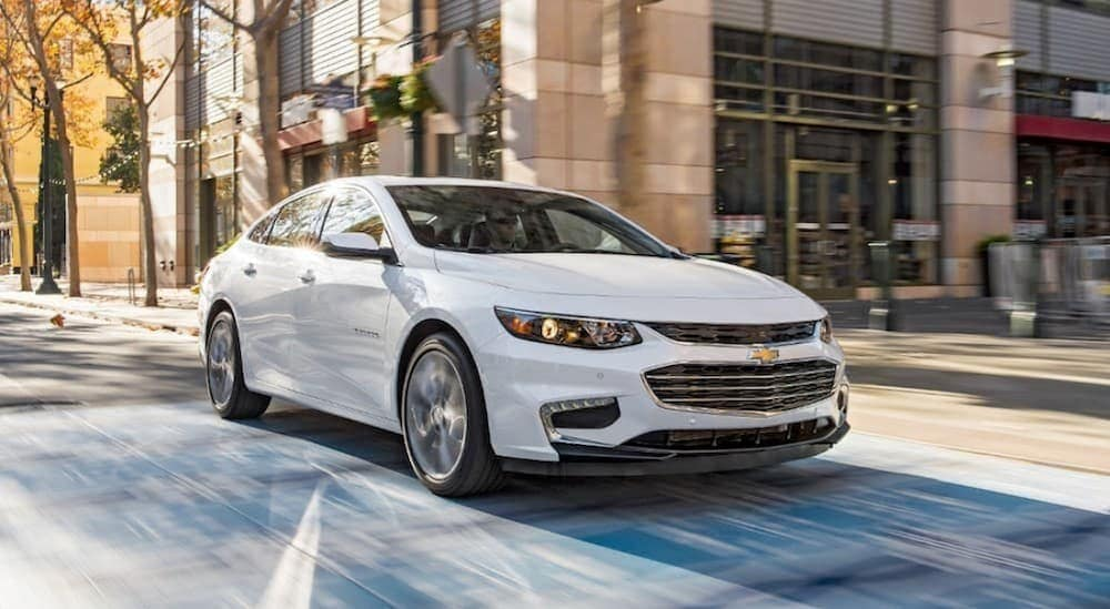 A white 2016 Chevy Malibu is driving down a city street near Bethlehem, PA.