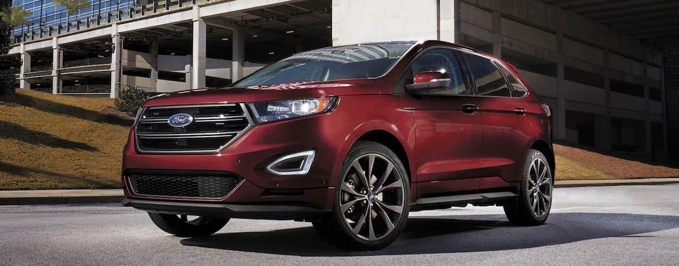 A red 2017 Ford Edge is parked near a parking garage in a city.