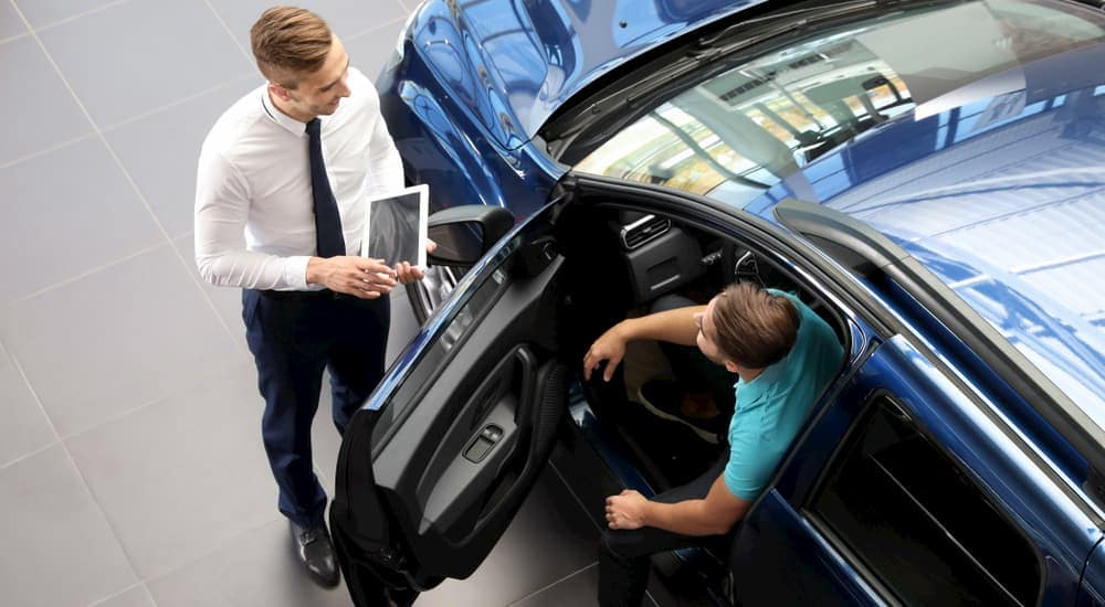 A salesman is showing a blue used car to a buyer who is sitting in the driver's seat.