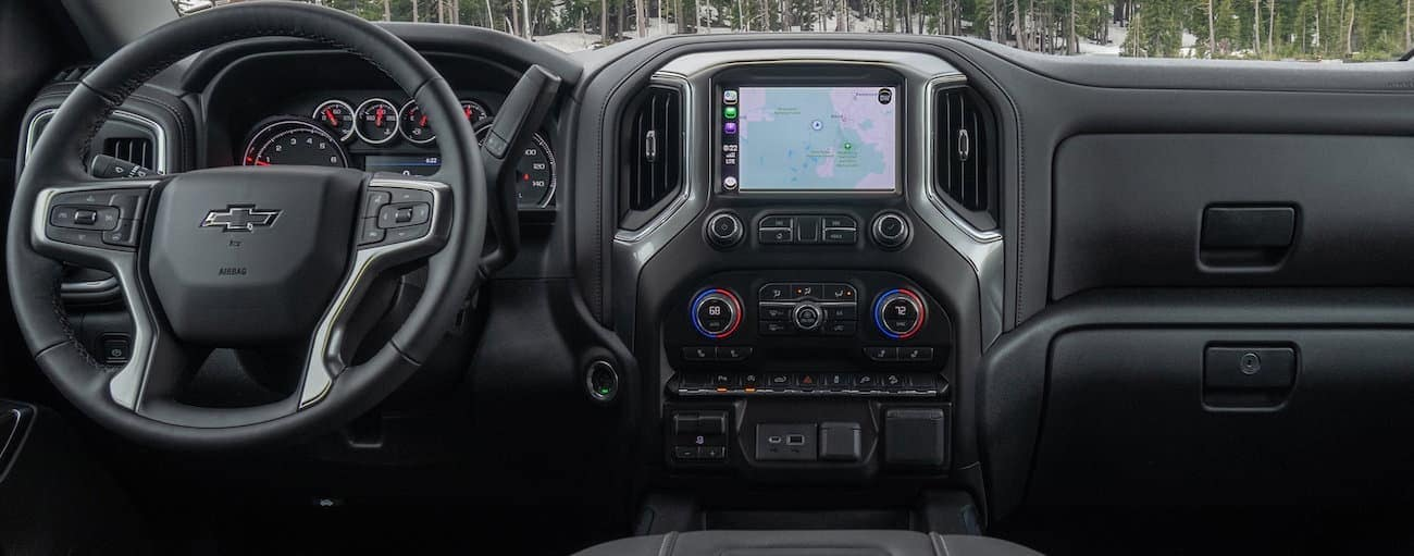 The front grey interior of a 2020 Silverado 1500 is shown with an infotainment system is shown.