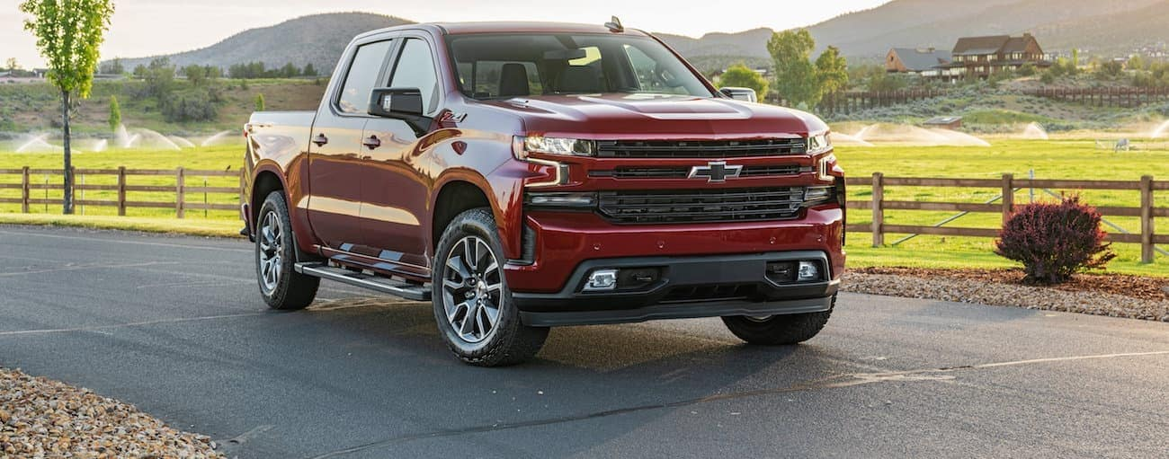 A red 2020 Chevy Silverado 1500, which wins when comparing the 2020 Chevy Silverado 1500 vs 2020 GMC Sierra 1500, is parked in front of a large farm near Bethlehem, PA.