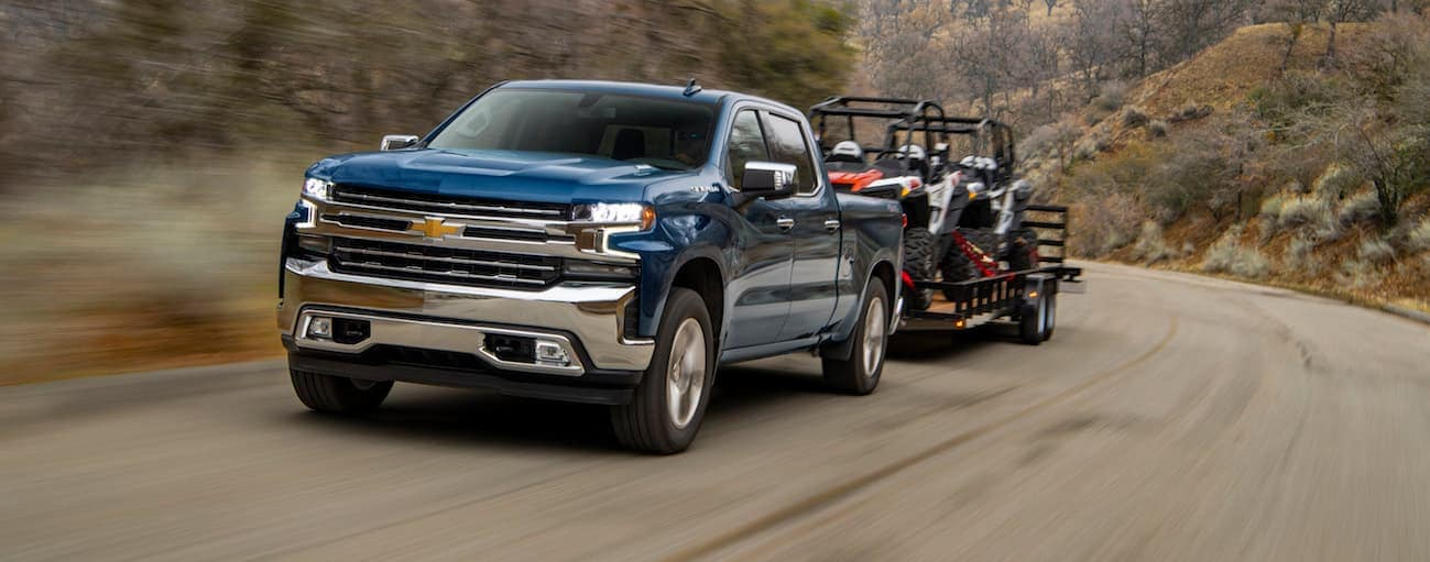 A blue 2020 Chevy Silverado 1500 is towing a trailer with side by sides on it on a dirt road.