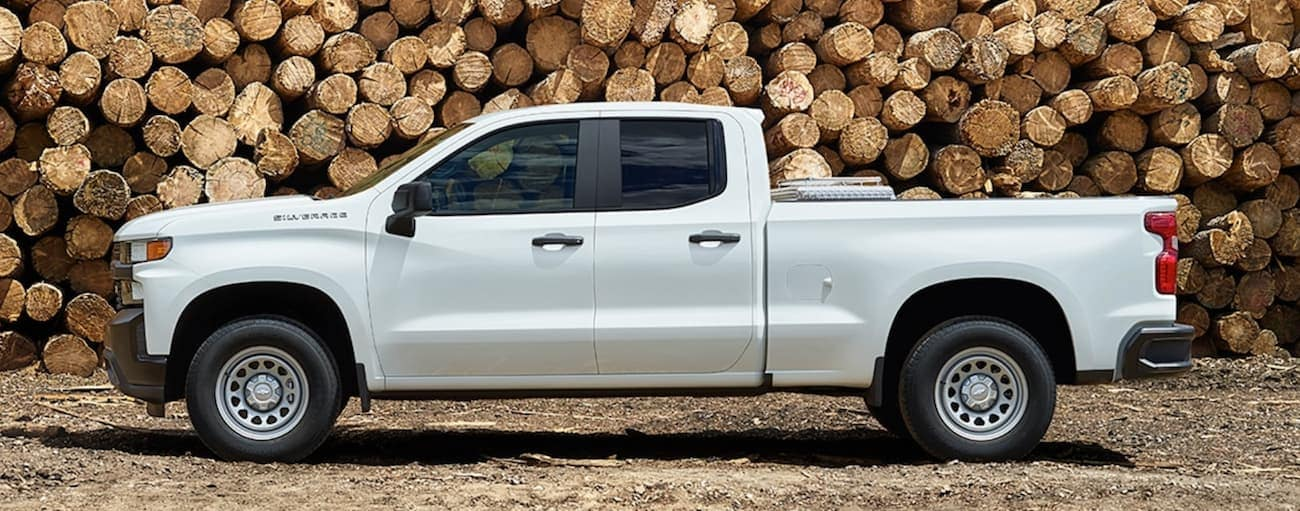 A white 2020 Chevy Silverado 1500 is shown from the side while parked in front of large cut logs.