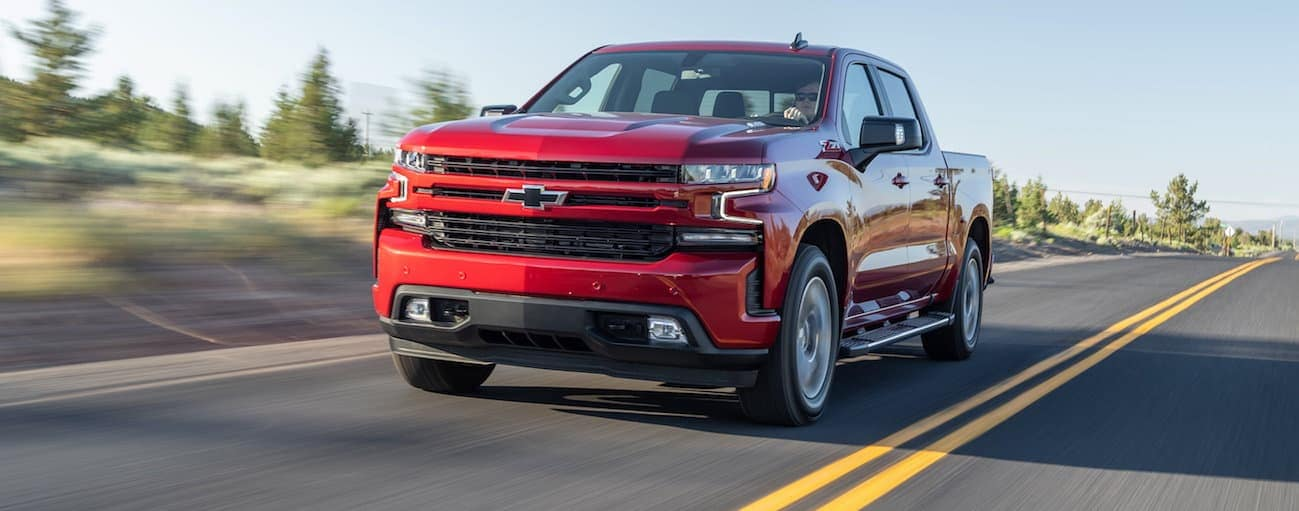 A red 2020 Chevy Silverado 1500 is driving on a tree lined road.