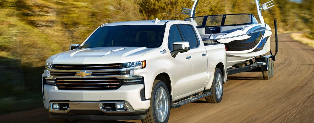 A white 2020 Chevy Silverado 1500, which wins when comparing the 2020 Chevy Silverado 1500 vs 2020 Toyota Tundra, is towing a boat near Bethlehem, PA.