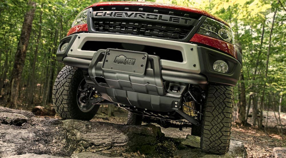 A red 2020 Chevy Colorado Bison is driving over large rocks in the woods.