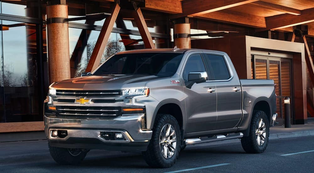 A silver Chevy Silverado Z71, which is a color you'll see when shopping for the Chevy Silverado Trail Boss vs Silverado Z71, is parked in front of an office building near Bethlehem, PA.