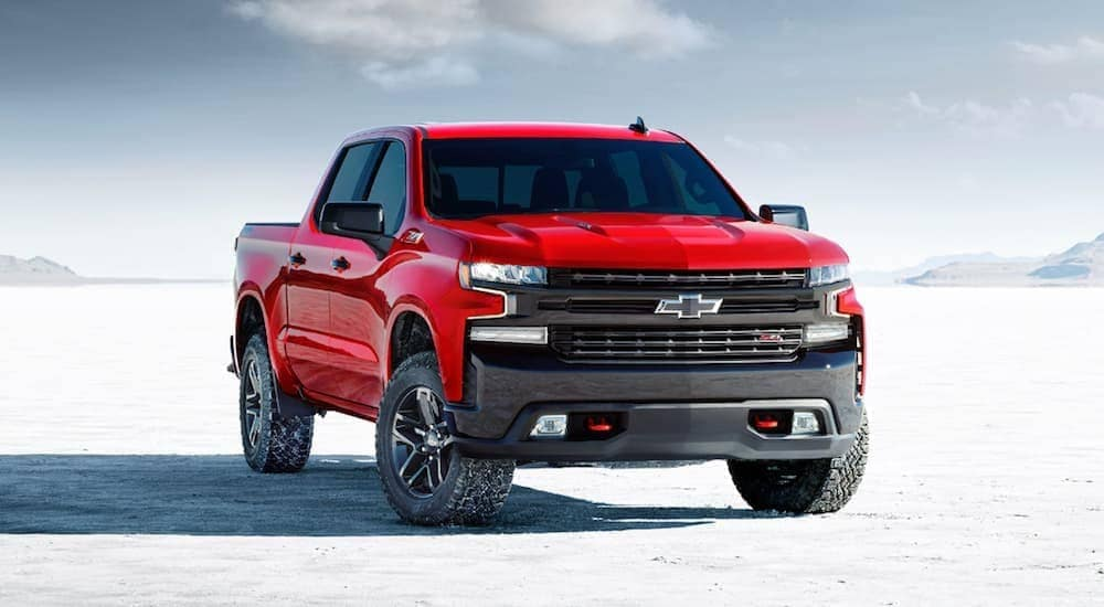 A red 2020 Chevy Silverado 1500 LT Trail Boss is parked on a flat salt land.