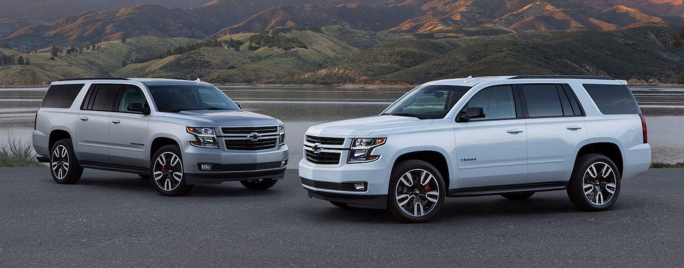 A silver Chevy Suburban and white Chevy Tahoe in front of a lake and mountains