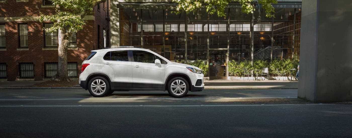 A white 2020 Chevy Trax under a bridge in front of a cafe