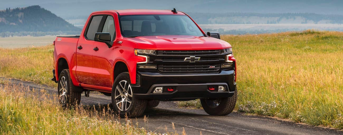 A red 2020 Chevy Silverado 1500 Trailboss, which wins when comparing the 2020 Chevy Silverado 1500 vs 2020 Nissan Titan, is parked on a dirt road.
