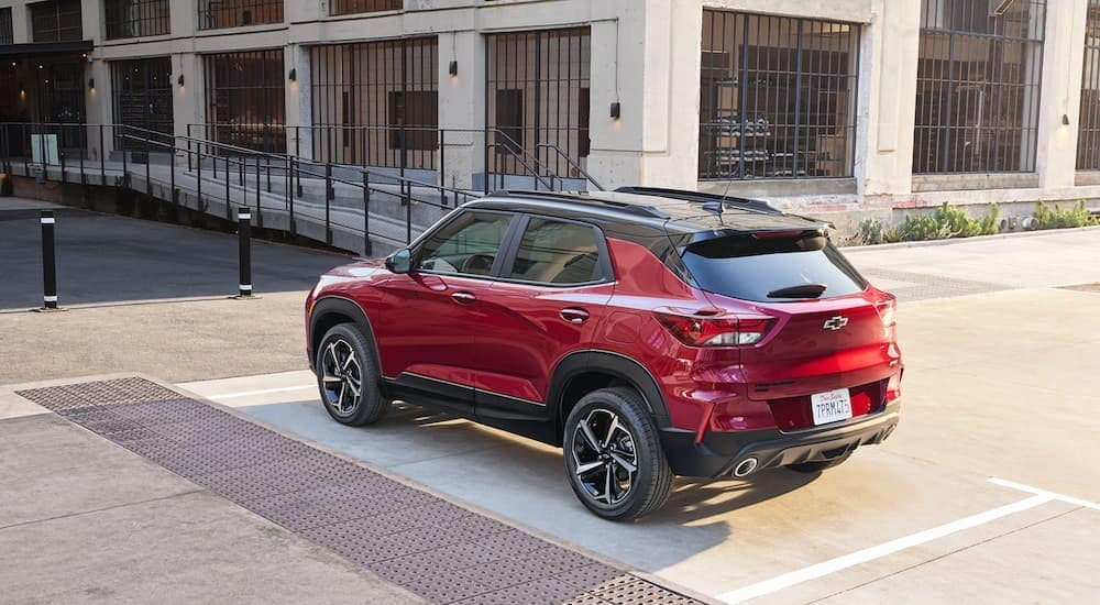 A red 2021 Chevy Trailblazer is shown from the rear in front of a city building.