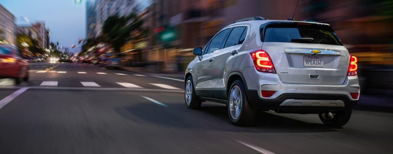 A white 2020 Chevy Trax, which wins when comparing the 2020 Chevy Trax vs 2020 Buick Encore, is driving on a city street at dusk.