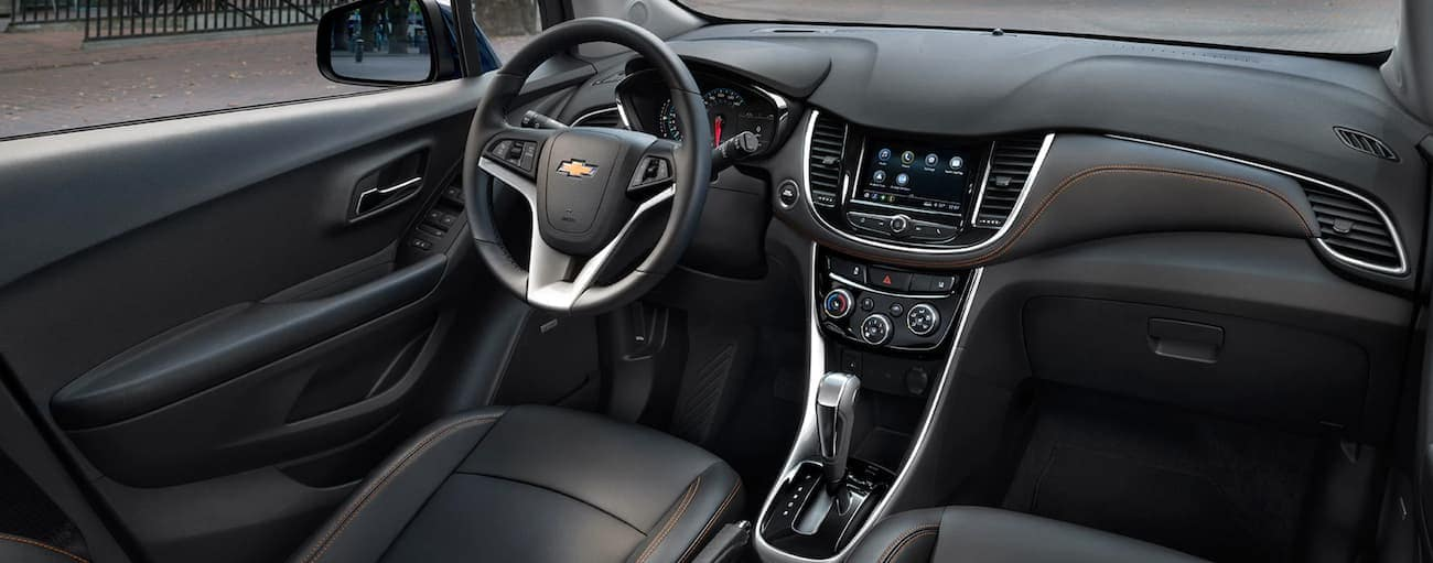 The black interior in a 2020 Chevy Trax is shown featuring the dashboard and infotainment screen.