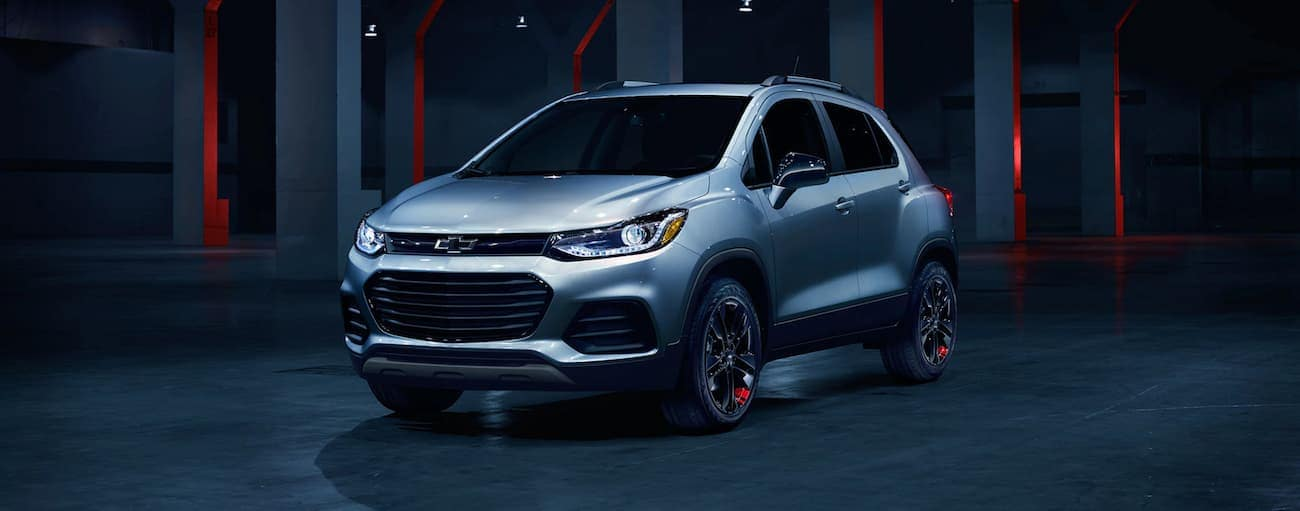 A silver 2020 Chevy Trax, which wins when comparing the 2020 Chevy Trax vs 2020 Ford EcoSport, is in a dark showroom.