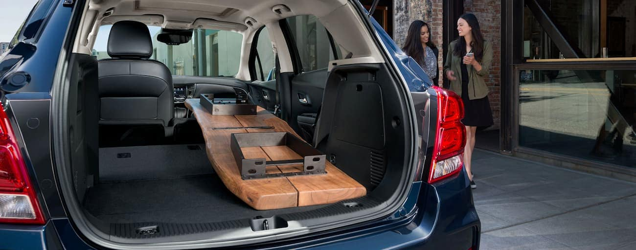 A wooden table is in the cargo area of a blue 2020 Chevy Trax.