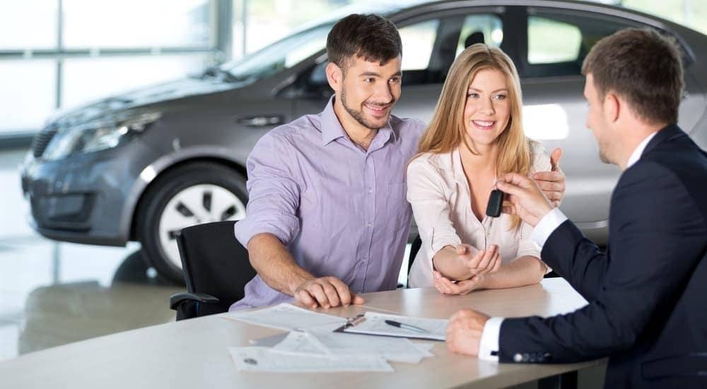 A salesman is taking keys from a couple in a car dealership in Bethlehem, PA.
