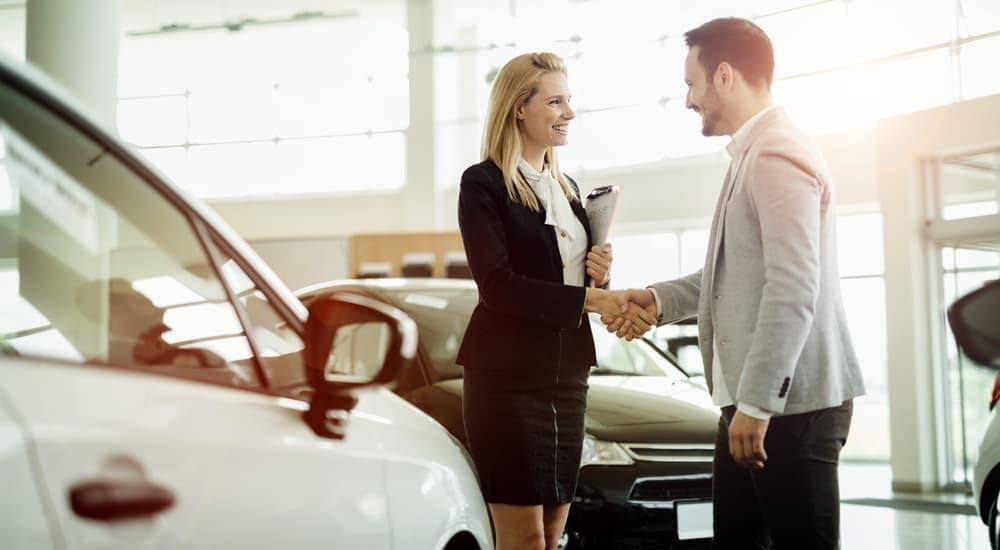 A man and woman are shaking hands in a dealership after she told him to 'sell us your car.'