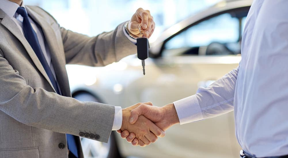 A salesman and a customer are shaking hands and exchanging keys in front of a white car.