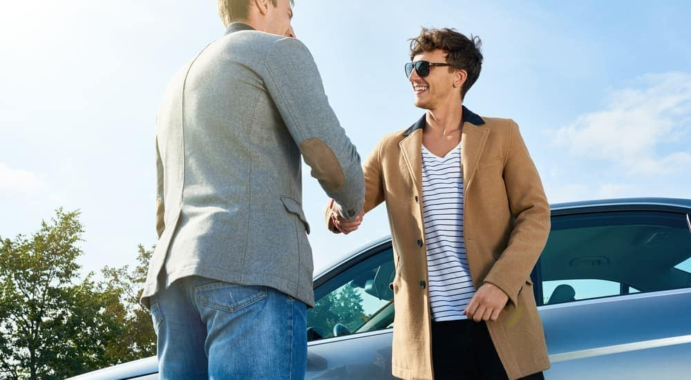 Two men are shaking hands in front of a used car.