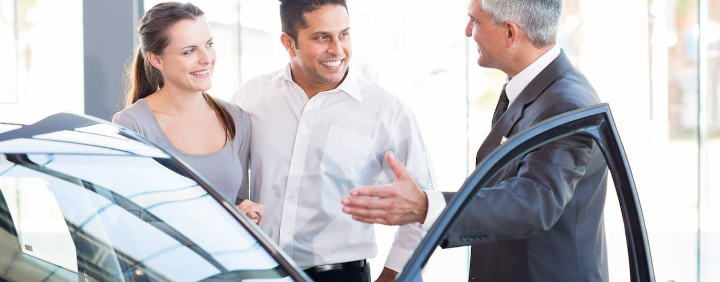 A salesman is saying 'sell us your car' to a couple in a Bethlehem, PA dealership.
