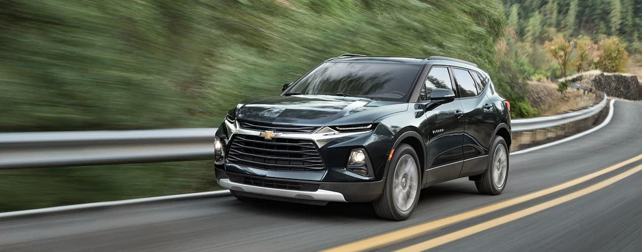A dark green 2020 Chevy Blazer is driving past trees on a winding road after winning the 2020 Chevy Blazer vs 2020 Ford Edge comparison.