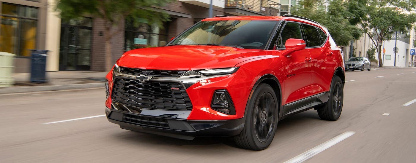 A red 2020 Chevy Blazer RS is driving on a city street after winning the 2020 Chevy Blazer vs 2020 Nissan Murano comparison.