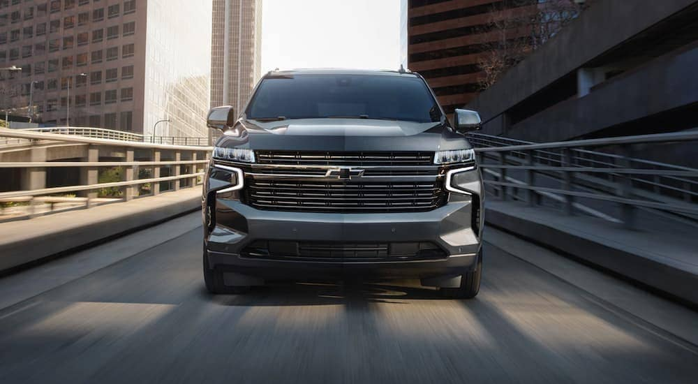 A grey 2021 Chevy Tahoe is shown from the front on a city highway.