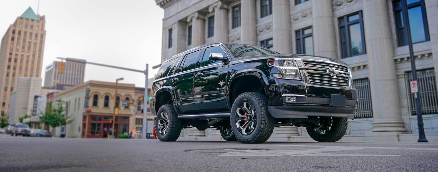 A 2018 Chevy Tahoe Black Widow edition built by SCA Performance Trucks is parked on a city street.