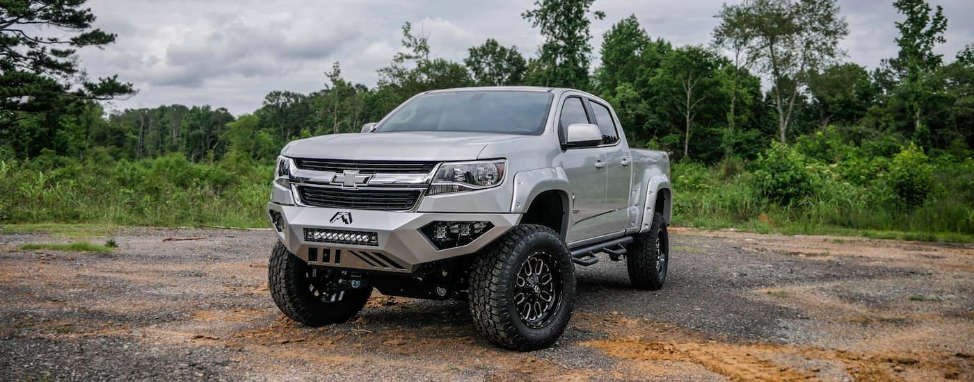 A silver 2018 Chevy Colorado Black Widow built by SCA Performance Trucks is parked in front of trees.