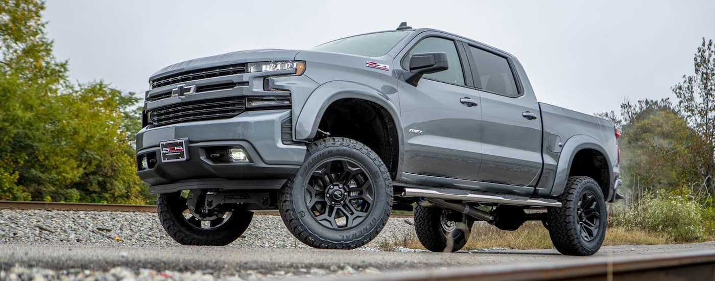 A grey 2019 Chevy Silverado Apex edition built by SCA Performance Trucks is parked between train tracks.