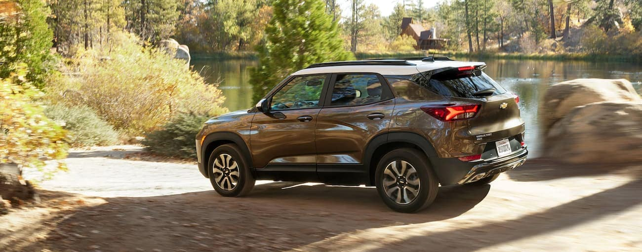 A white and brown 2021 Chevy Trailblazer is driving on a dirt road past a pond after winning the 2021 Chevy Trailblazer vs 2020 Chevy Trax comparison.