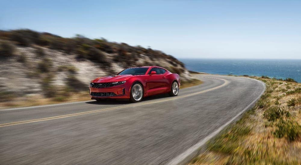 A red 2020 Chevy Camaro is driving on a coastal highway.