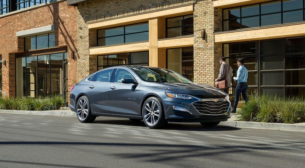 A grey 2020 Chevy Malibu is parked in front of a tan building after leaving a Chevy dealer in Bethlehem, PA.
