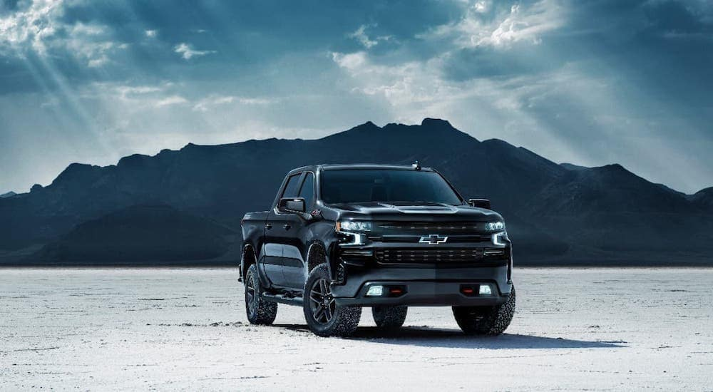 A black 2020 Chevy Silverado 1500 Midnight edition is parked in front of mountains.