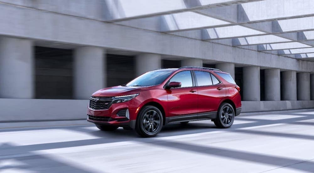 A red 2021 Chevy Equinox is driving under an overpass and to a Chevy dealer in Bethlehem, PA.