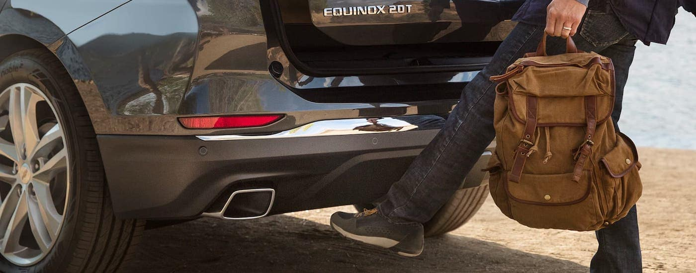 A closeup shows someone using the foot-activated automatic liftgate available on a gray 2020 Chevy Equinox.