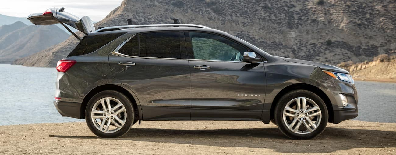 A grey 2020 Chevy Equinox is parked in front of a lake and mountains after winning the 2020 Chevy Equinox vs 2020 Mazda CX-5 comparison.