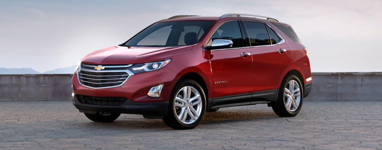 A red 2020 Chevy Equinox is parked in front of a low grey wall near Bethlehem, PA.