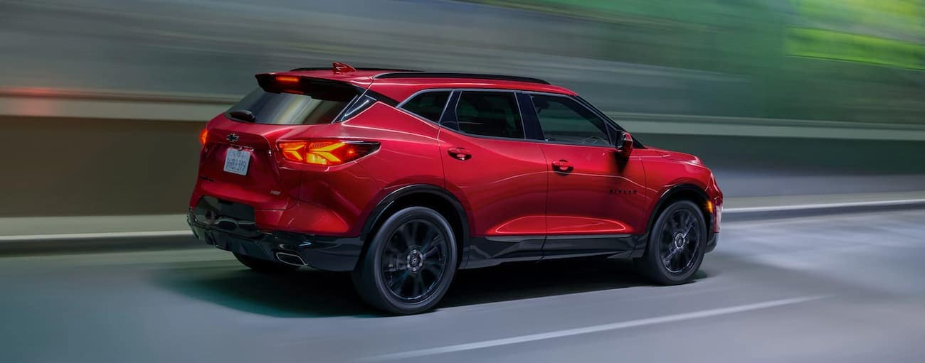 A red 2021 Chevy Blazer RS is driving out of a very blurred tunnel.