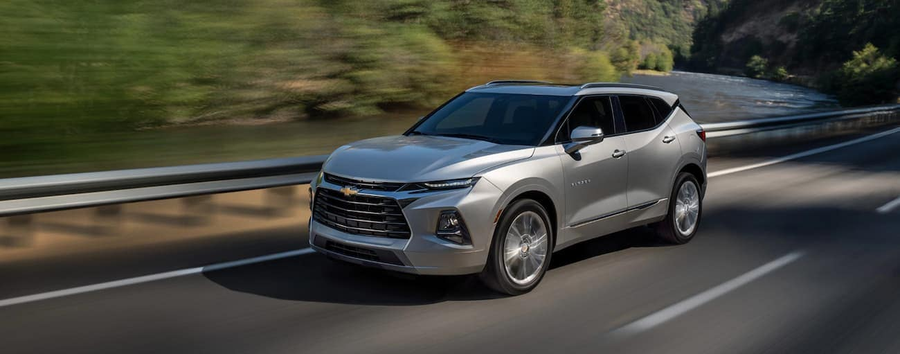 A silver 2021 Chevy Blazer is driving past a guardrail and trees.