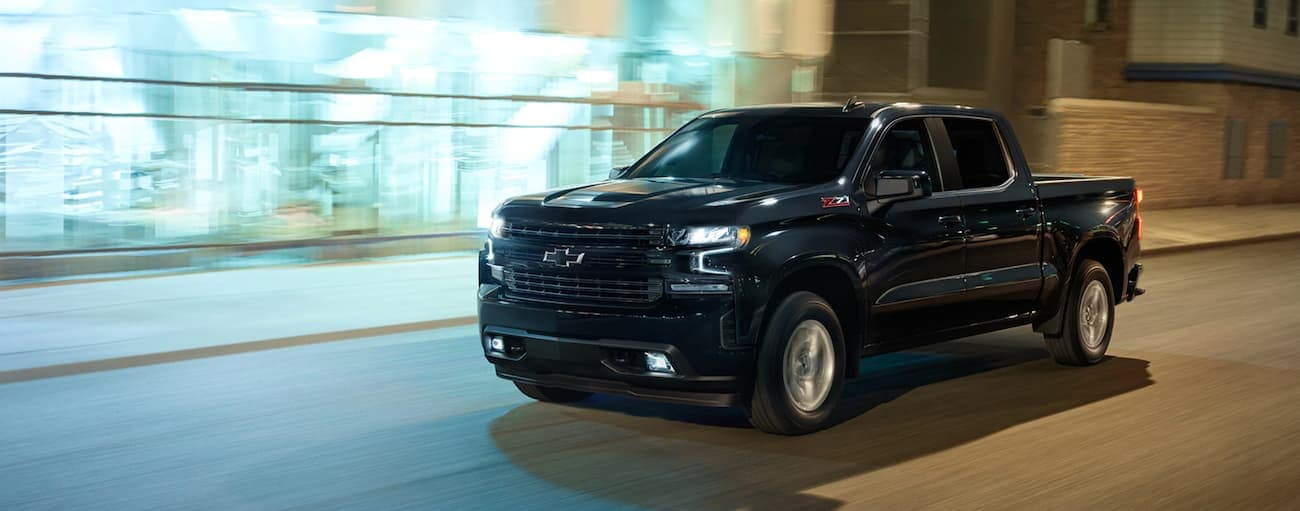 A black 2021 Chevy Silverado 1500 is driving past a city building at night.