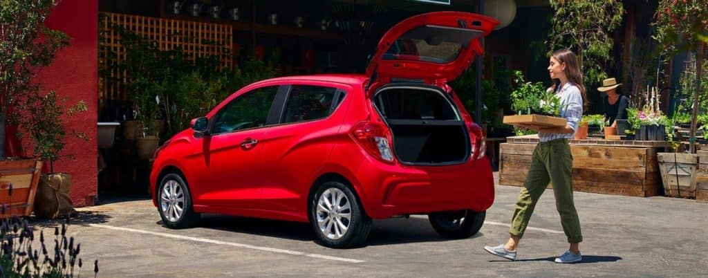 A woman is carrying a plant to the open trunk of a red 2021 Chevy Spark.