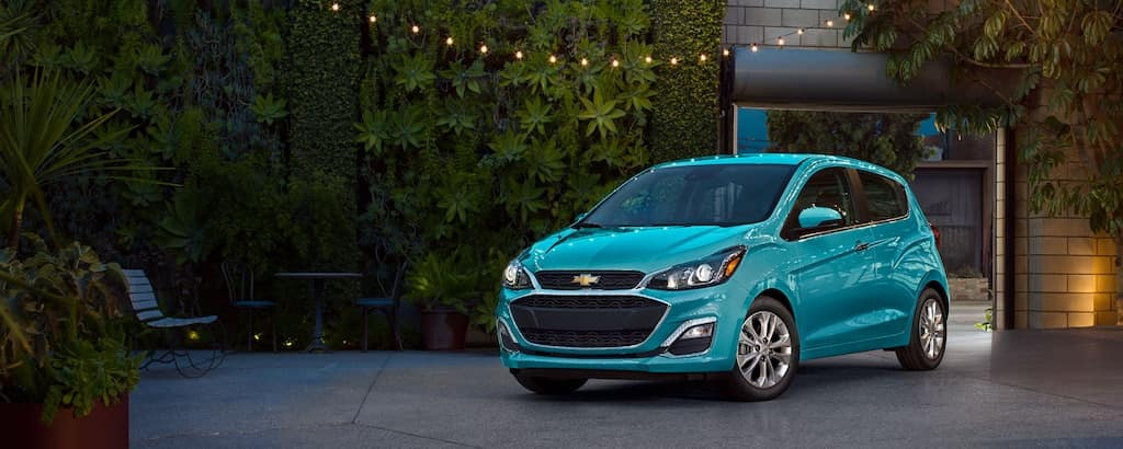 A blue 2021 Chevy Spark is parked in front of a wall of plants.