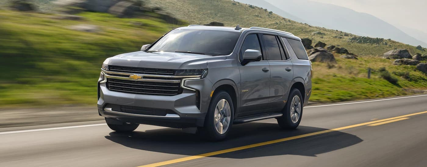 A grey 2021 Chevy Tahoe is driving past grassy hills.